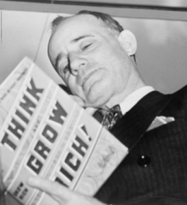 "Napoleon Hill holding book 1937"" by New York World-Telegram and the Sun Newspaper staff photographer."